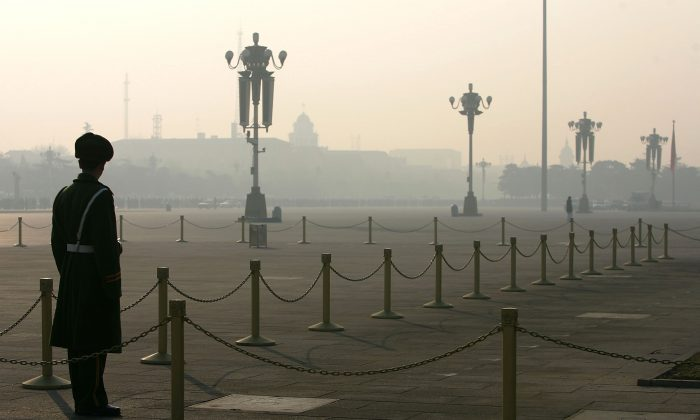 A Chinese police officer stands guard at Tiananmen Square during fog on January 1, 2005 in Beijing, China. (Cancan Chu/Getty Images)