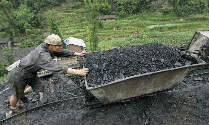 A miner pushes a cart containing coal at a mine in Qianwei county in China's southwestern province of Sichuan, 25 May 2005. (Liu Jin/AFP/Getty Images)