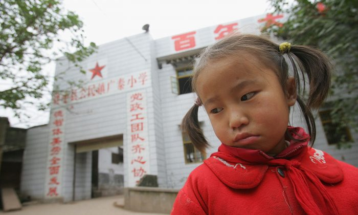 A Chinese orphan Lin Chuanxiu, whose parents died of AIDS, stares at the ground outside the elementary school of Gongmin Township, 2005 in Zizhong of Sichuan Province, southwest China. (China Photos/Getty Images)