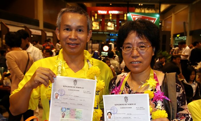 TO FREEDOM IN NORWAY: Li Jianhui and his wife Dai Ying show their newly acquired asylum visas to Norway to the press, prior to flying to Oslo from Don Muang International Airport in Bangkok in the early morning of Jan. 24, 2005.  (The Epoch Times)