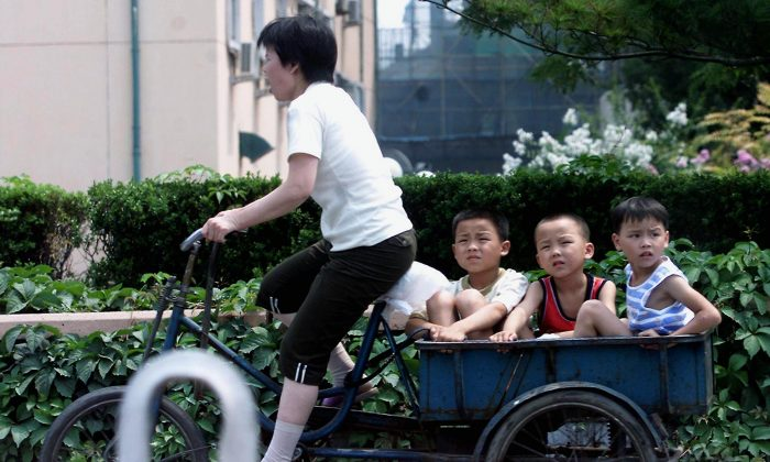 A woman peddles hard as she takes three young boys on her tricycle along a street in Beijing on July 18, 2001. (Goh Chai Hin/AFP/Getty Images)