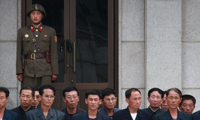 North Koreans stand as a North Korean soldier guards the border village of Panmunjom, between North and South Korea, on Sept. 29. (Lee Tae-kyung/Chosun Daily News via Getty Images)