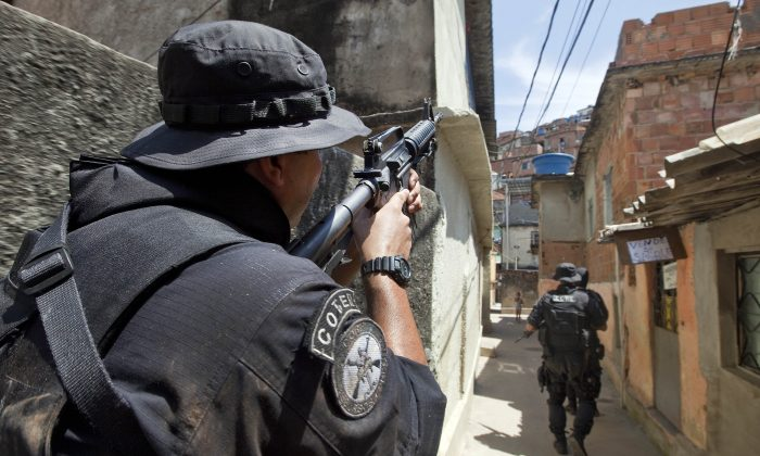 THE WAR CONTINUES: Coordination of special resources policeman covers his comrades as they patrol at Morro do Alemao shantytown in Rio de Janeiro, Brazil, on Nov. 29. Police scoured the sewers under Rio's sprawling slums Monday for hundreds of drug traffickers who fled an unprecedented military onslaught on the favelas (slums) that netted 40 tons of narcotics but few arrests. (Jefferson Bernardes/AFP/Getty Images)