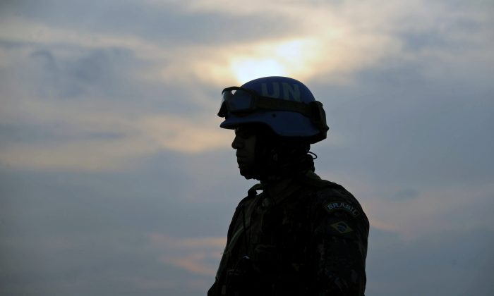A Brazilian soldier with the MINUSTAH force stands during a patrol at a shantytown in Port-au-Prince, Haite, on March 2, 2013. (Vanderlei Almeida/AFP/Getty Images)