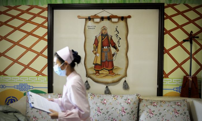 A nurse walks past a portrait of Genghis Khan, founder and Great Khan of the Mongol Empire, in a maternity ward at Antai Hospital in Beijing, China, on Nov. 28, 2012. (Wang Zhao/AFP/Getty Images)