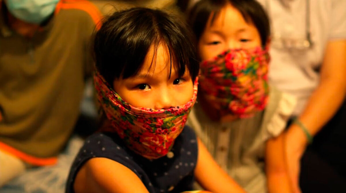 """two children wearing scarves over their faces in """"Contagion"""""""