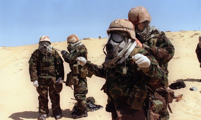 U.S. soldiers from the 4th Regiment of Marines help each other to dress full anti-chemical equipments on Aug. 23, 1990, during a training operation in the Saudi desert a few days after the Iraqi army entered the Kuwait. (Gerard Fouet/AFP/Getty Images)