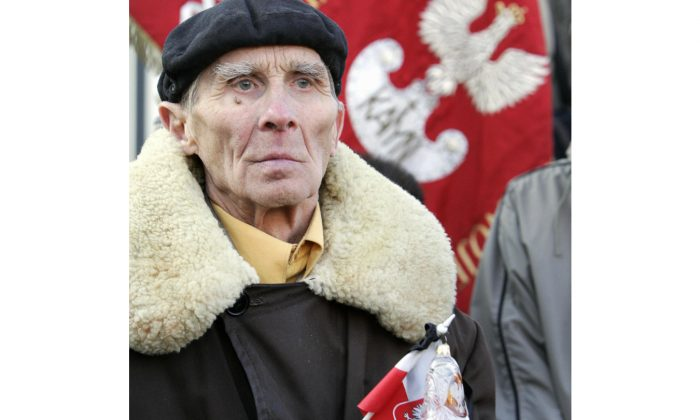 An elderly man holding a Polish nation flag during a demonstration in front of Russia's embassy in Warsaw on March 15, 2005, against the decision of Russia's chief military prosecutor to stop the investigation into the 1940 Katyn Forest massacre, in which the Soviets summarily execute over 20,000 Poles. (Janek Skarzynski/AFP/Getty Images)