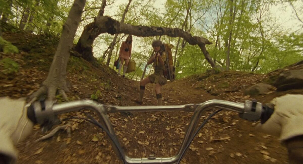 """girl and boy in woods approached by bicycler in """"Moonrise Kingdom"""""""