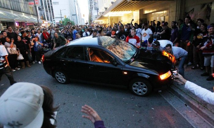 Rioters in downtown Vancouver try to flip a car after the Vancouver Canucks lost the Stanley Cup on June 15, 2011. Miles Craig, founder of Canada's Temperance Foundation, kicked off a temperance campaign on the first anniversary of the riots. (Bruce Bennett/Getty Images)