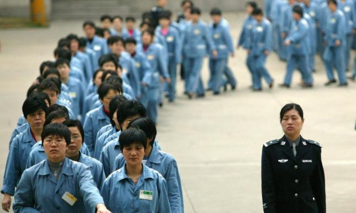 Prisoners walk beside a guard at a jail in Nanjing, China, in a file photo.(STR/AFP/Getty Images)