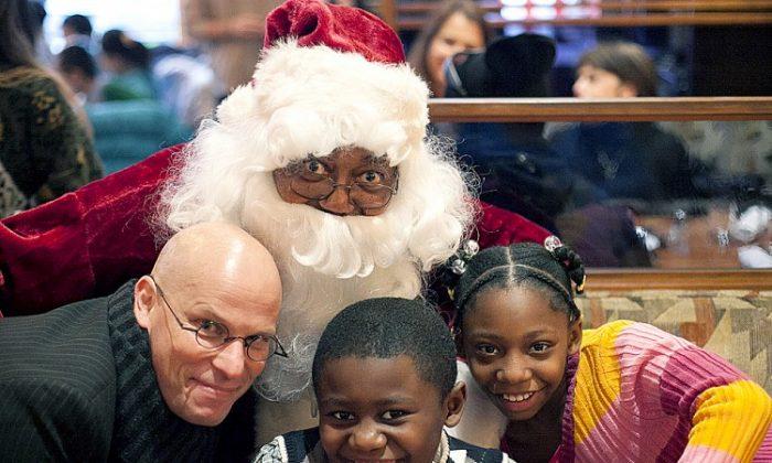 Robert Harris, a volunteering Santa Claus, and Thomas Kauertz, serve children at City Hall Restaurant's annual Christmas Eve lunch for the homeless on Dec. 24. (Deborah Yun/Epoch Times Staff)
