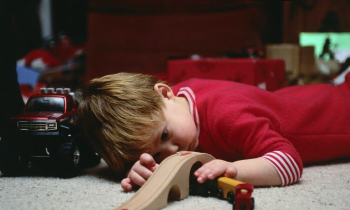 A young boy plays quietly and intently with his wooden train set. When choosing gifts for children this holiday season, consider toys that are fun as well as spark children's creativity, and be vigilant about product safety. (Ablestock.com/Photos.com)