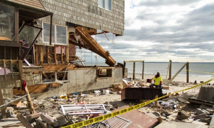 A gas company worker surveys the damage of a beachfront home in the Sea Gate community in Brooklyn on Saturday, Nov. 3, 2012. The huge wave from the surge of Superstorm Sandy completely destroyed many of the beach front homes. (Kristen Meriwether/The Epoch Times)