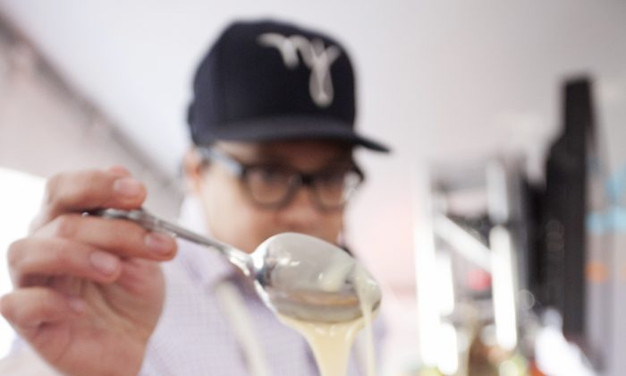 Dale Talde, Chef at Pork Slope and Thistle Hill Tavern, tops his signature shaved ice dessert dish with more condensed milk at the Malaysian Kitchen event in Bryant Park on Feb. 21, 2013. (Deborah Yun/Epoch Times)