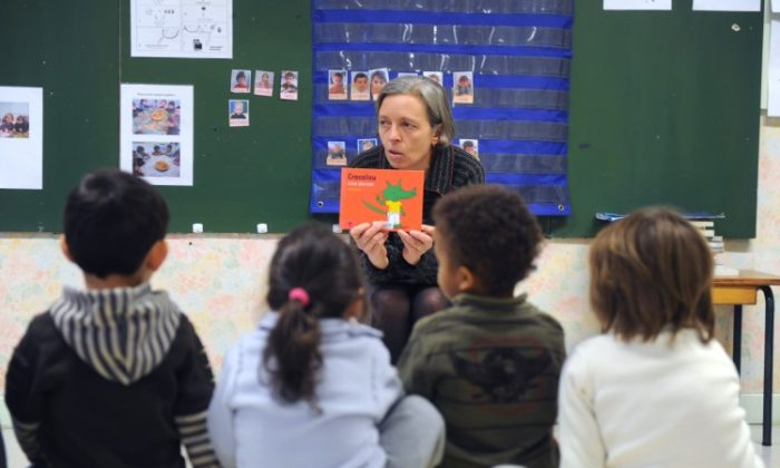 A teacher reads a book to her kindergarten class. An education professor is calling for improved working conditions for teachers, many of whom are leaving the profession due to issues such as overwork and bullying by parents. (Eric Cabanis/AFP/Getty Images)