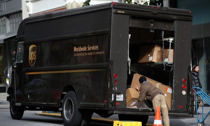 A UPS worker unloads packages from his truck on Dec. 20, 2012 in San Francisco, Calif. (Photo by Justin Sullivan/Getty Images)