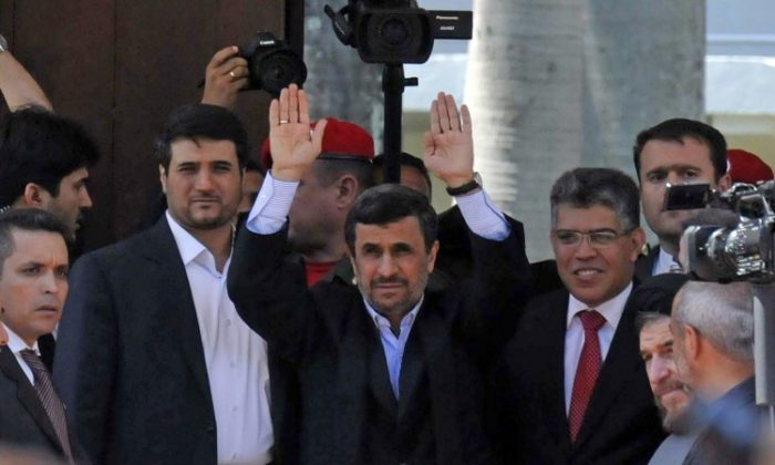 Iranian President Mahmoud Ahmadinejad (C) waves alongside Venezuelan Minister of Foreign Affairs Elias Jaua (C-R) outside of the funeral of the late President Hugo Chavez, in Caracas, on March 8, 2013. (STR/AFP/Getty Images)