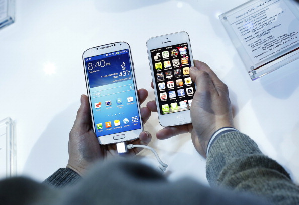 A visitor holds a Samsung Electronics Co. Galaxy S4 smartphone, left, next to an Apple Inc. iPhone 5 during the Galaxy S4 unveiling in New York March 15. (Victor J. Blue/Bloomberg via Getty Images)