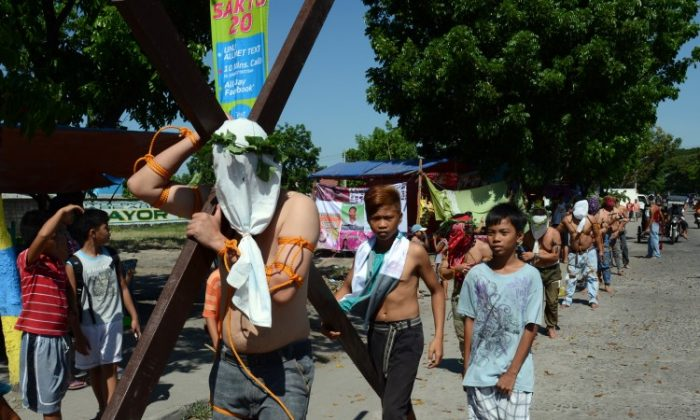 A penitent carries a cross while other flagellate themselves as they participate in symbolic ceremonies which commemorate Jesus Christ's crucifixion and resurrection on Holy Thursday in Angeles City, Pampanga province north of Manila on March 28, 2013. (Ted Aljibe/AFP/Getty Images)