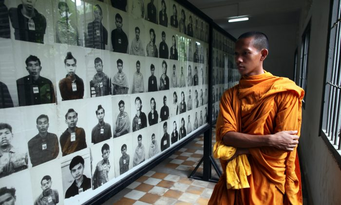 A Cambodian monk looks at photos of victims of the Khmer Rouge regime on display at the Toul Sleng Genocide Museum in Phnom Penh Province, Cambodia, on July 25, 2010. (Paula Bronstein/Getty Images)