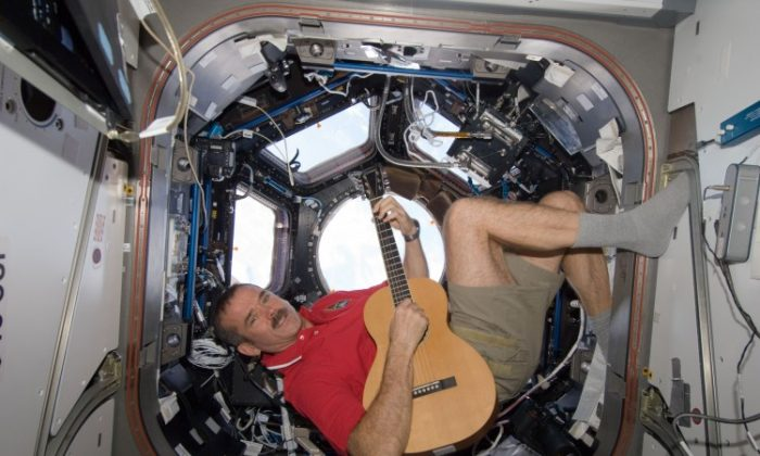 Canadian Space Agency astronaut Chris Hadfield strums his guitar in the International Space Station's Cupola observatory module on Dec. 25, 2012. Hadfield, a long-time member of an astronaut band called Max Q, later joined with the other five Expedition 34 crew members in a more spacious location to provide an assortment of Christmas carols for the public. (NASA)