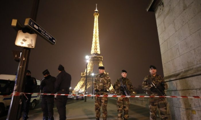 French police officers and soldiers stand guard near the Eiffel Tower in Paris on March 30, 2013. The Eiffel Tower was evacuated in the evening on March 30 after an anonymous caller announced an attack. (Thomas Coex/AFP)