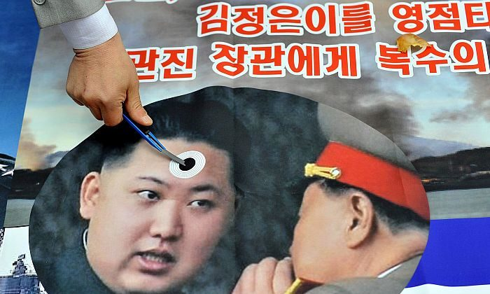 A South Korean activist marks a picture of young North Korean leader Kim Jong Un (L) during an anti-North Korea rally in Seoul last week. The North Korean military on Tuesday threatened to target the United States and U.S. bases raising concerns the young leader may go beyond the usual posturing. Jung Yeon-Je/AFP/Getty Images)
