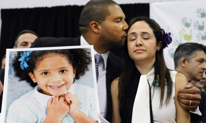 Jimmy Greene, left, kisses his wife Nelba Marquez-Greene as he holds a portrait of their daughter, Sandy Hook School shooting victim Ana Marquez-Greene, at a news conference at Edmond Town Hall in Newtown, Conn in this file photo. (AP Photo/Jessica Hill)