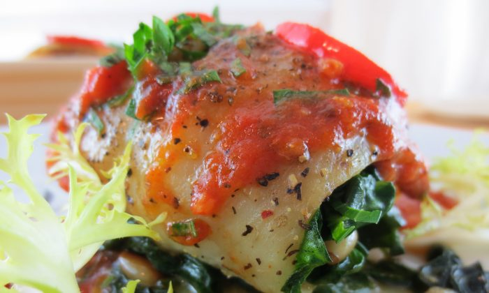 Fish fillet filled with sautéed spinach and pine nuts and covered with a tomato sauce. (Maria Baciu/The Epoch Times)