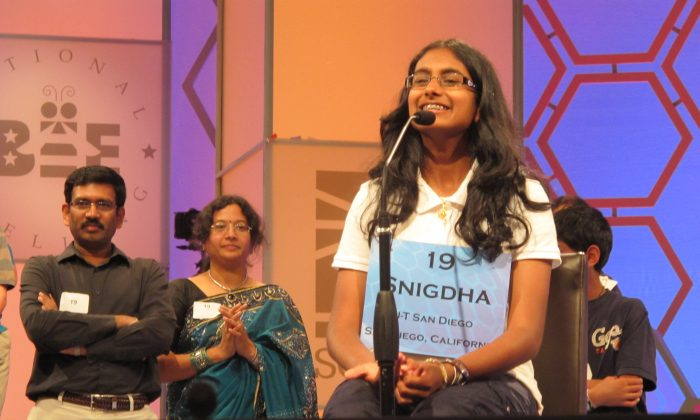 """Snigdha Nandipati, 14, of San Diego, California, speaks to reporters on May 30, 2012—with her parents in the background—after winning the 85th Scripps National Spelling Bee. She spelled """"guetapens,"""" correctly, a word that means ambush, snare, or trap. Now the Spelling Bee includes vocabulary questions in the preliminary and semifinal rounds. (Robert MacPherson/AFP/GettyImages)"""