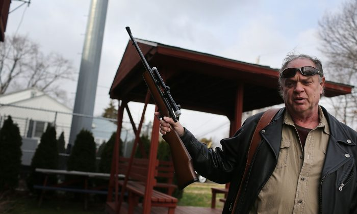 Holding one of three rifles he's turning in, Bob Coyle stands outside of a gun buyback event in Bridgeport, Conn. A gun manufacturer based in the state says its moving because of new gun control laws that are too strict. (Spencer Platt/Getty Images)