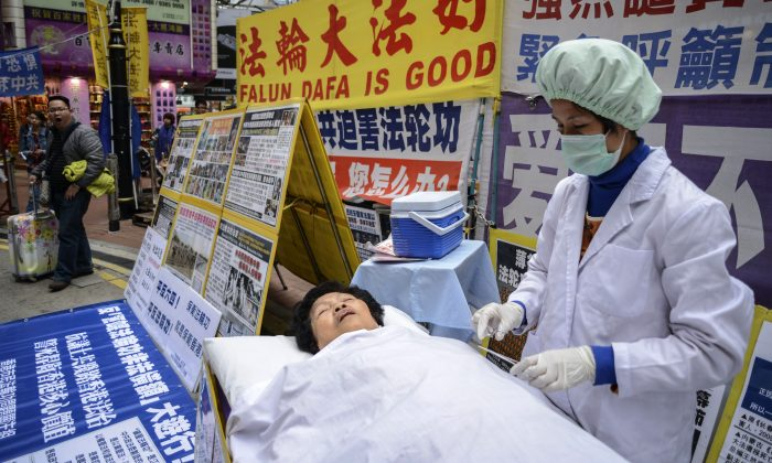 Falun Gong members perform a mock forced organ removal in a shopping district of Hong Kong on Jan. 12, 2013. (Antony Dickson/AFP/Getty Images)
