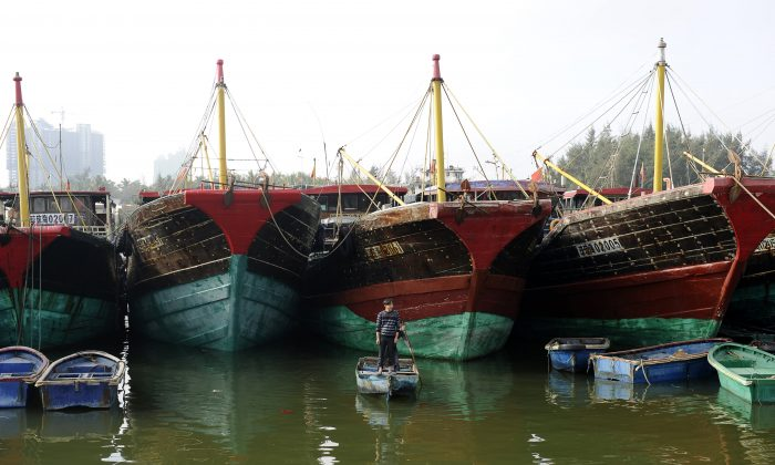 A Chinese fisherman in front of fishing vessels in the sea town of Tanmen, in China's southern Hainan Province, on Jan. 21, 2013. With Beijing claiming a huge swath of the strategically crucial South China Sea, Hainan's fishermen and tour agencies are at the forefront of the dispute. (Wang Zhao/AFP/Getty Images)