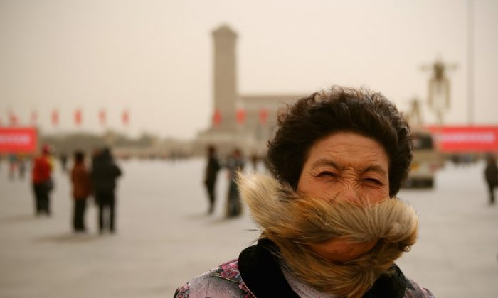 A Chinese tourist walks on the Tiananmen Square during the sandstorm on March 9, 2013 in Beijing, China. (Photo by Feng Li/Getty Images)