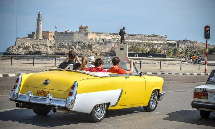 Tourists take a ride in a fully restored Mercury along the coast in Havana on March 18, 2013. Luxury is slowly reappearing in Cuban society after half a century of egalitarianism and austerity, brought upon by the economic reforms of Cuban President Raul Castro. (Adalberto Roque/AFP/Getty Images)