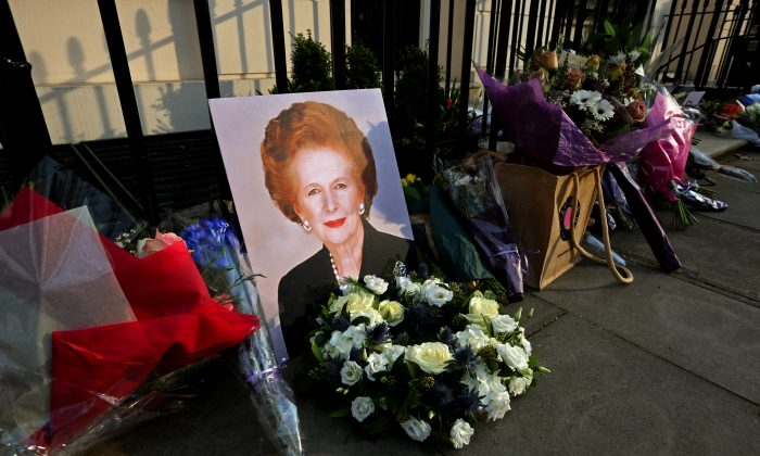 A portrait of former Prime Minister Margaret Thatcher is left next to floral tributes outside her residence in Chester Square in London, England, on April 8, 2013. (Peter Macdiarmid/Getty Images)