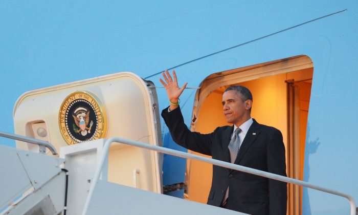 President Barack Obama waves as he steps off Air Force One upon arrival April 8, 2013 at Andrews Air Force Base in  Maryland. (MANDEL NGAN/AFP/Getty Images)