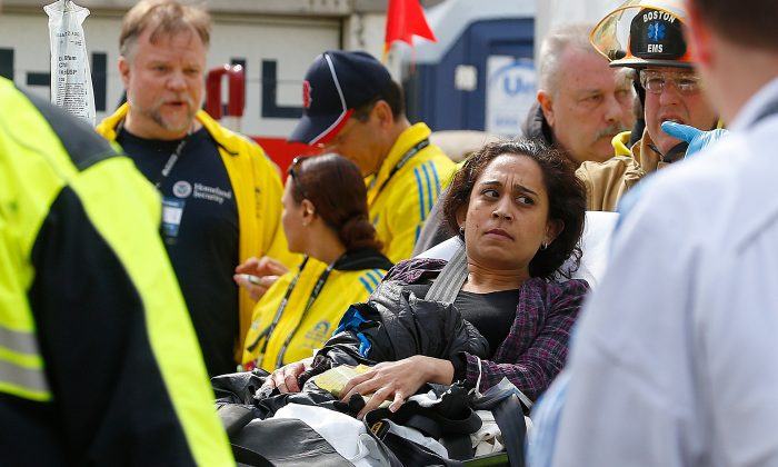 A woman is loaded into an ambulance after she was injured by one of three bombs exploded during the 117th Boston Marathon near Copley Square on April 15, 2013 in Boston, Massachusetts. (Jim Rogash/Getty Images)