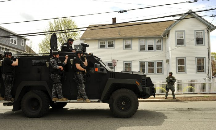 A police SWAT team search houses for the second of two suspects wanted in the Boston Marathon bombings takes place April 19, 2013 in Watertown, Massachusetts. (TIMOTHY A. CLARY/AFP/Getty Images)