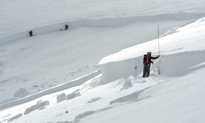 Scott Toepfer, right, a member of the Colorado Avalanche Information Center or CAIC, takes depth measurements every 50 feet at the crown of an avalanche on April 21, 2013. Snow sports are risky, but there are ways to lesson the risk.   (AP Photo/The Denver Post,Helen H. Richardson)