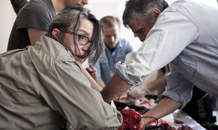 (L-R) Carol Dysinger and Robert Nickelsberg perform a medical procedure, using a chicken carcass for training. (Samira Bouaou/The Epoch Times)