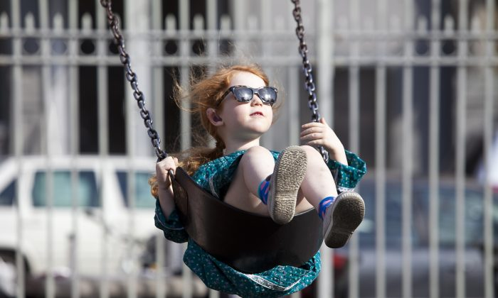 Grace Gibbon, 4, enjoys a swing at the Thompson St. playground in SoHo on Monday. Temperatures reached into the 70s for the first time this spring. (Samira Bouaou/The Epoch Times)