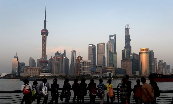 Tourists watch the sunset over the Pudong financial district of Shanghai on April 15. China's economic growth slowed to 7.7 percent in the first quarter, data showed, below expectations and fuelling concerns that a recent recovery is faltering on subdued overseas demand. (Mark Ralston/Getty Images)