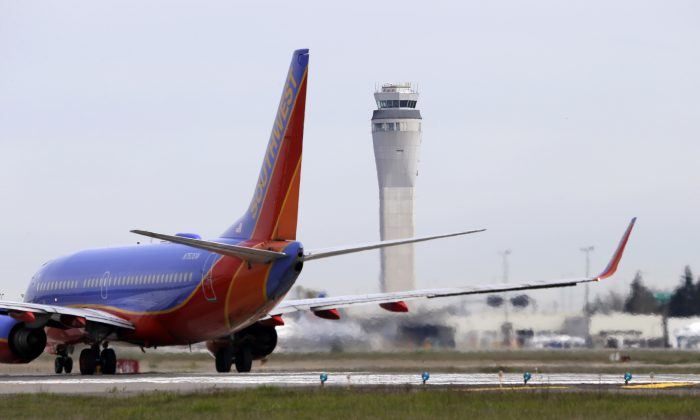 This photo taken April 23, 2013 shows a Southwest airlines jet waiting to depart in view of the air traffic control tower at Seattle-Tacoma International Airport in Seattle. (AP Photo/Elaine Thompson)