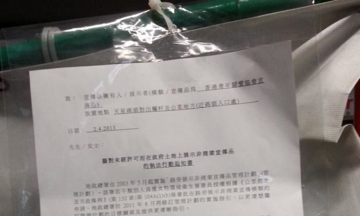 A Hong Kong government notice placed on a banner belonging to the Hong Kong Youth Care Association, a communist front group, said that the exhibit was in violation of the law and had to be removed, lest the group face stiff fines. (Expose the Evil Deeds of the Hong Kong Youth Care Association)