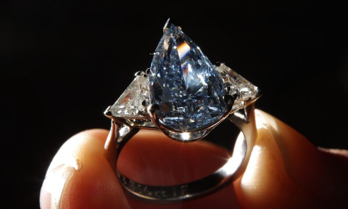 An employee displays a 5.16 carat pear shaped fancy vivid blue diamond ring at Sotheby's on March 8, 2010 in London, England. (Peter Macdiarmid/Getty Images)