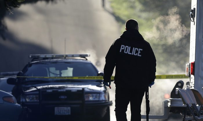 A police officer carries a shotgun and what appears to be a shell casing as officers collect evidence from the scene of an overnight shooting that left five people dead. (AP Photo/Ted S. Warren)