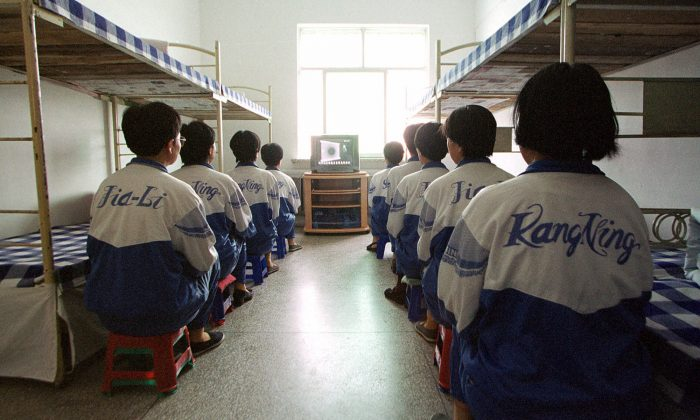 Falun Gong practitioners are shown in Masanjia labor camp watching a video meant to re-educate them during a propaganda tour arranged by the camp authorities on May 22, 2001. One of the tortures used on the practitioners involves handcuffing them awkwardly between bunk beds, and then yanking the beds apart, causing excruciating pain. (AP Photo/John Leicester)