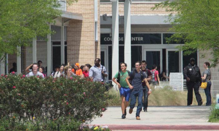Students run from the Lone Star College's Cypress-Fairbanks campus Tuesday, April 9, 2013, in Cypress, Texas. At least 14 people were hurt in a stabbing at the campus.  (AP Photo/Houston Chronicle, James Nielsen)